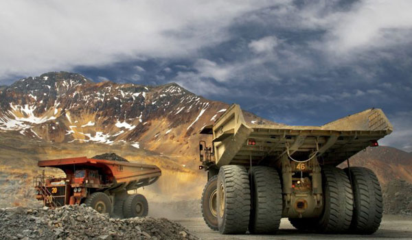 Two mining trucks in a quarry with mountains in the background